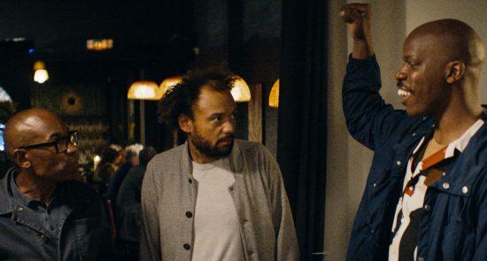 Visuel du film Tout simplement noir. Trois hommes viennent sortir d'un restaurant.